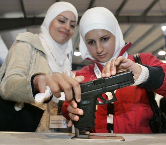 طالبتان تتفحصان مسدسا لدى زيارتهما الى معرض سوفكس
