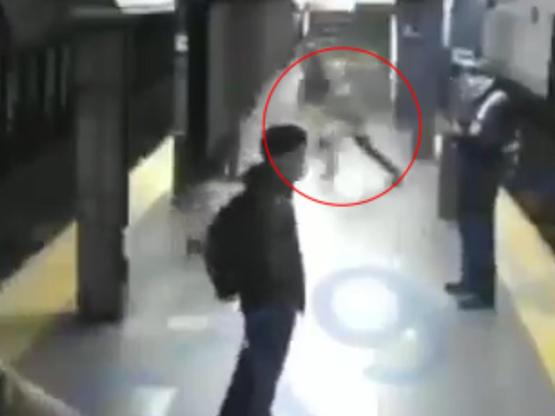 شاب يدفع امرأة تحت عجلة قطار متحرك - فيديو
